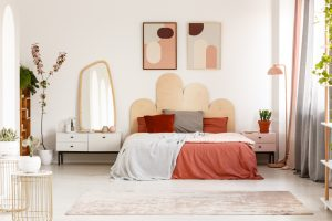Modern,Posters,Above,Bed,With,Headboard,In,Pastel,Bedroom,Interior